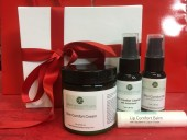 White luxury box with red ribbons containing Skin Comfort Oil, Skin Comfort Cream, Skin Comfort Cleanser, and Lip Comfort Balm.